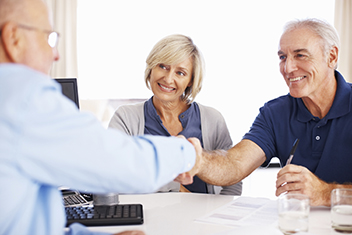 Happy elderly couple seal a deal with their personal financial advisor
